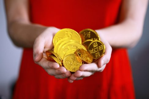 women in red dress holding gold bars and coins